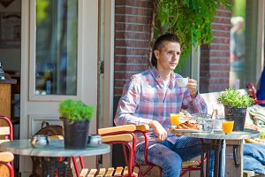 Happy young man sitting in outdoor cafe at european city drinking coffee