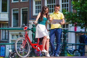 Young tourists on bikes looking at map in european city