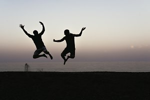 Happy of two friends jumping.