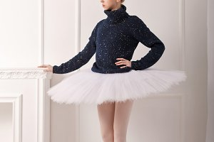 Ballerina standing at fireplace
