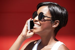 People, technology and lifestyle concept. Happy hipster dark-skinned girl talking on mobile phone, smiling, receiving good news while posing against red wall with copy space for your advertisement