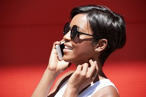 Headshot of beautiful stylish young woman with short pixie hairstyle wearing round shades making phone calls, smiling and flirting while having conversation with her boyfriend, touching her neck
