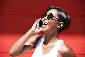 Half profile of beautiful young woman wearing casual white top and stylish shades with happy expression and mouth wide open, laughing while having a phone conversation using generic smart phone