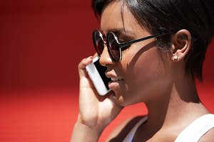 Close up isolated profile of attractive young female with perfect healthy skin wearing hipster sunglasses having serious phone call, listening attentively, with lips parted. Play of light and shadow