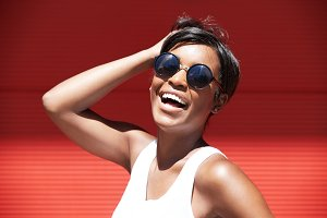 Headshot of beautiful young woman wearing casual white top and stylish shades looking and smiling at the camera with happy cheerful expression, mouth wide open, touching her short brunette hair