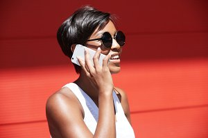 People and technology concept. Half profile portrait of stylish brunette businesswoman wearing round sunglasses, answering phone calls, talking to her partner, discussing business with happy look