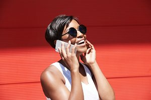 Beautiful self-confident fashionable young female with short brunette hair wearing stylish round shades, smiling while talking on cell phone to her best friend, laughing at some joke, looking up