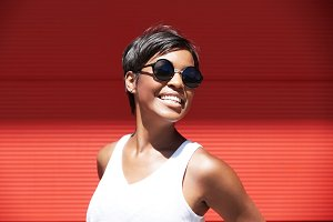 Cute female model with short hairstyle looking at the camera, showing her ultra-white smile, having fun while posing against red wall background with copy space for your text or advertising content