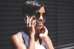 Happy attractive female student girl wearing round hipster shades talking on smart phone to her parents, sharing her achievement after passing successfully final exams, smiling, touching her neck