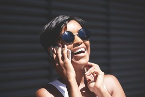 Technology and communication concept. Headshot of fashionable dark-skinned brunette woman with short haircut wearing round sunglasses, laughing while talking on smart phone with cheerful expression