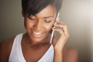 Headshot of attractive young African female with healthy clean skin talking on mobile phone, inviting her friends for a party, smiling, looking down. Pretty woman having a phone conversation