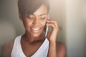 Close up portrait of beautiful young woman with healthy skin and short hair wearing white top, making phone calls, talking to her boyfriend using electronic device, smiling, showing ultra-white teeth