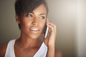 Technology and communication concept. Close up shot of beautiful dark-skinned brunette woman with short haircut making a phone call, ordering food delivery using generic electronic device indoors