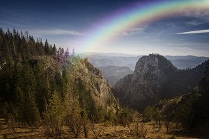 Rainbow over mountain with big cliff