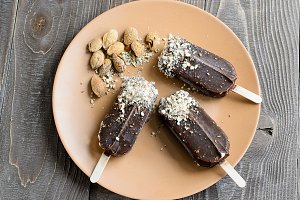 Chocolate popsicles with nuts on a brown wood background