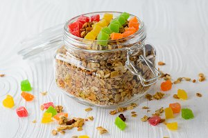 Muesli with dried fruit and candied fruit on a white wood background, selective focus.