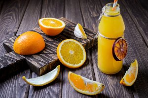 Composition with bottle of orange juice and fruits on a brown wooden background. Selective focus.