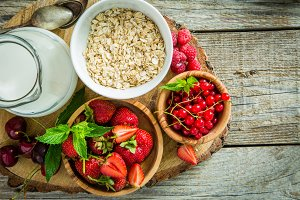 Oatmeal with berries on rustic wood background
