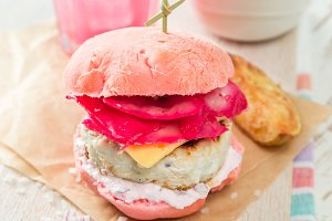 Pink chicken grill burger on wood background