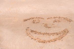Handwrite face on the sand beach