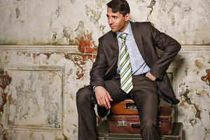 Businessman sitting on suitcases