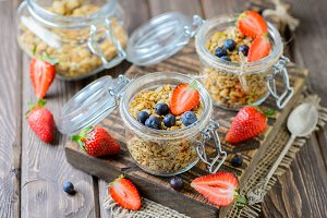 Healthy breakfast of muesli, berries on dark wood background.
