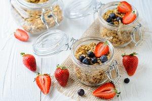 Healthy breakfast of muesli, berries on white wood background.
