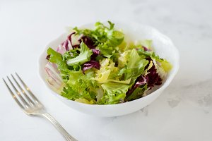 Mixed fresh vegetable salad (green iceberg lettuce, radicchio and frisee) in white bowl on a white background