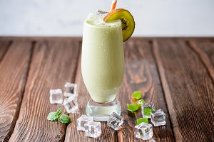 Fresh pistachio cocktail with kiwi on a wooden background