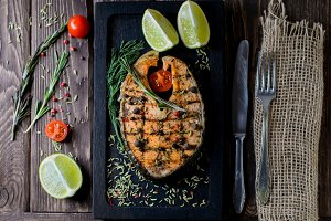 Grilled salmon on black board on wooden background