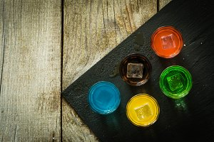 Selection of colorful shot drinks on white wood background