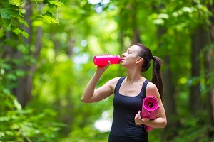 Young active fitness woman with mat and bottle of water outdoors