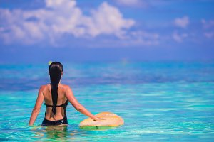 Beautiful fitness surfer woman surfing during summer vacation
