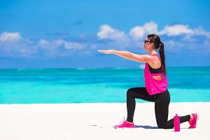 Healthy athlete woman working out doing exercise on tropical white beach