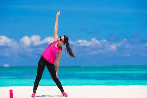 Healthy athlete woman working out doing exercise on tropical white beach in her sportswear