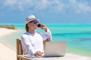 Young businessman with computer and cell phone on white beach
