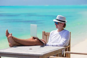 Young man with tablet computer on tropical beach