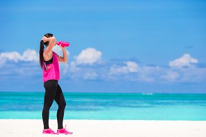 Fit young woman drink water on white beach