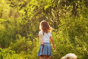 Little girl walking with a dog