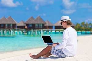 Young man working on laptop at tropical beach near water villa