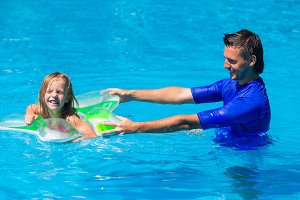 Happy active family, young father and cute daughter playing in swimming pool enjoying summer vacation