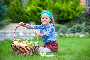 Little girl with baskets full of tomatoes