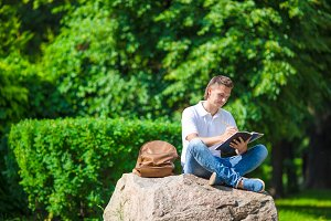 Young student in park outside with notebook and backpack