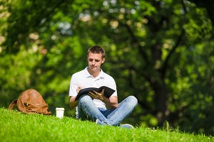 University student studying for exams outdoors in the park. With him his books, notebook, backpack and coffee.