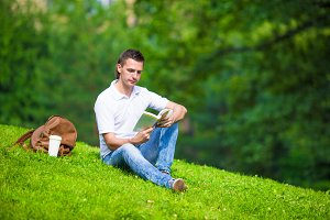 Young man relaxing with coffee in park reading a book