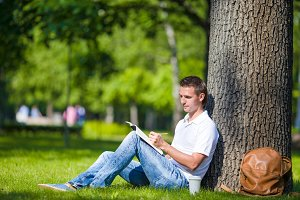 Young man relaxing near tree with coffee reading a book