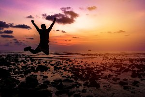 man Happy jump in sunset on beach