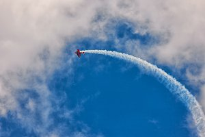 Red biplane aircraft in the blue sky