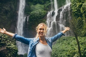 Tourist with tropical waterfall