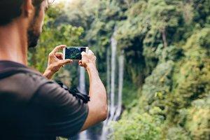 Man taking photos of waterfall
